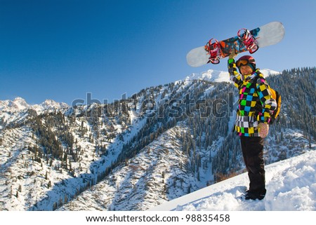 An image with snowboarder with a helmet and glasses on the background of high snow-mountain Alps in Grindelwald, Swiss - stock photo