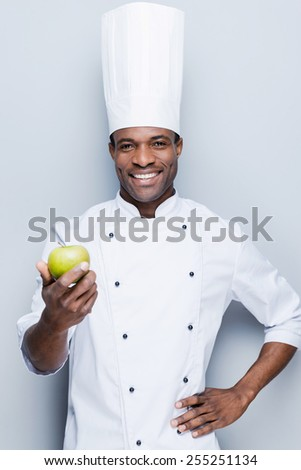 An important ingredient for fruit salad . Confident young African chef in white uniform stretching out green apple and looking at camera with smile while standing against grey background - stock photo