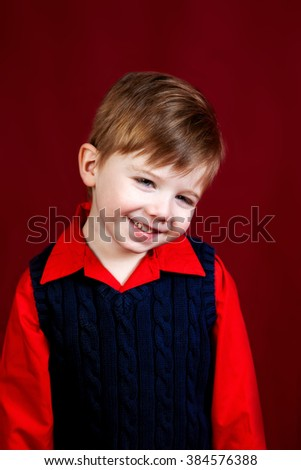 An in studio portrait of a shy boy on a deep red backdrop.   He is wearing a dark blue sweater vest over a red, collared shirt.  It could be a holiday look for Christmas or Valentine's Day.