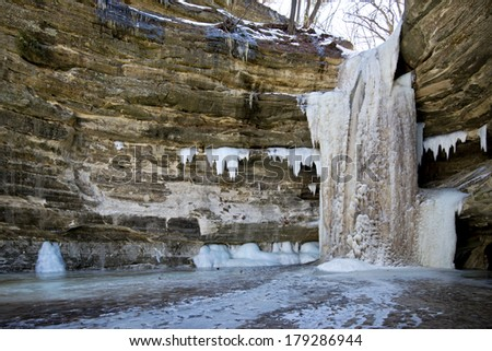 An incredible winter sight, the St. Louis Canyon waterfall freezes into a solid fifty foot high ice fall during cold Illinois winters. - stock photo