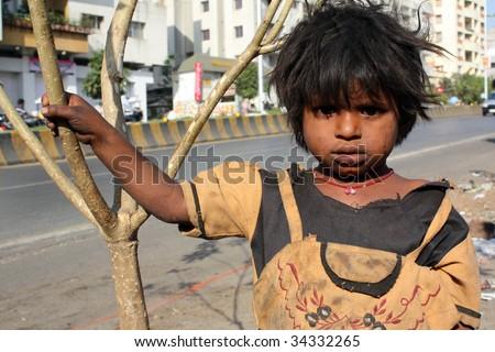 An Indian beggar girl standing under the harsh sun on a streetside. - stock photo