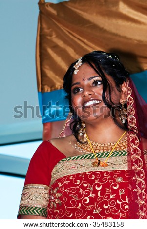 An indian bride in a red sari smiles - stock photo