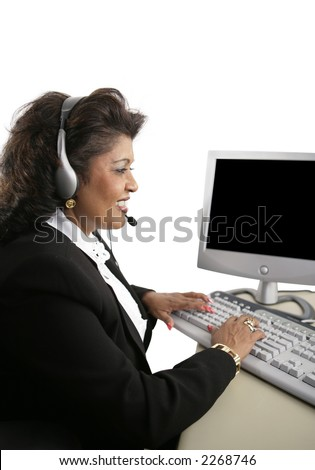 An Indian customer service representative at the computer wearing a headset.  Isolated on white. - stock photo