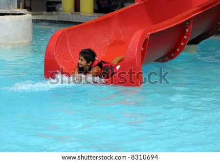 An indian kid having fun at a water slide