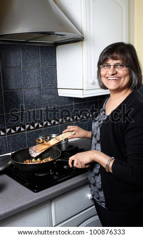 An indian lady in the kitchen making a curry