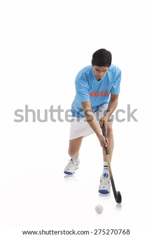 An Indian male player playing hockey isolated over white background - stock photo