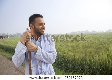 An Indian man looking away while holding a stick - stock photo