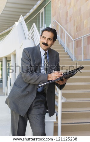 An Indian middle aged businessman holding folder while leaning on railing and looking away