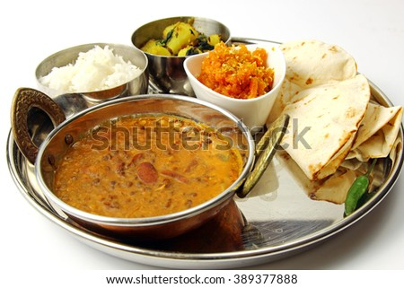 An Indian platter with dal makhani, potato and spinach bhaji, rice, gajar halwa and chapati on white background.