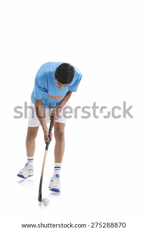 An Indian player playing hockey isolated over white background - stock photo