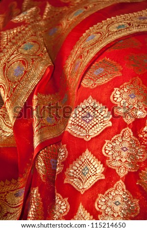 an Indian Sari with orange fabric and Gold thread - stock photo