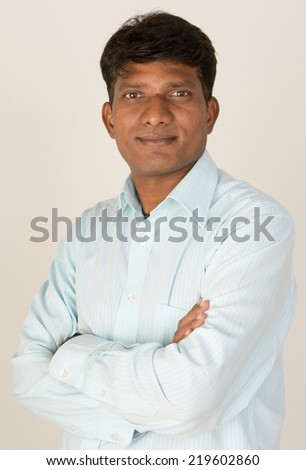 An Indian / South Asian business executive with folded arms looking to camera. On grey background. - stock photo