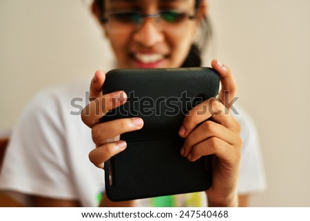 An Indian teenager chatting happily on a black smart mobile phone. Happy young girl in T-shirt. - stock photo