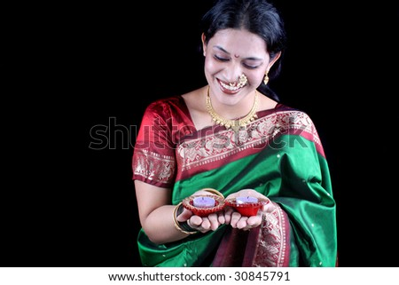 An Indian woman in a traditional green sari holding diwali candles on the occasion of Diwali festival, on black studio background.