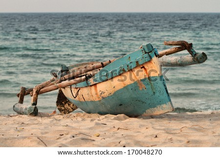 An indigenous fishing boat or canoe or type of dhow is lying on the beach sand of Pemba mozambique. - stock photo