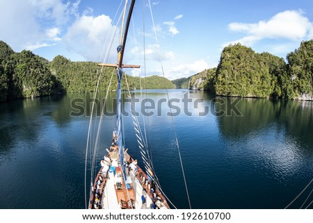 An Indonesia Pinisi schooner cruises through a narrow channel in Raja Ampat, Indonesia. This region is known as the heart of the Coral Triangle and is high in marine diversity. - stock photo