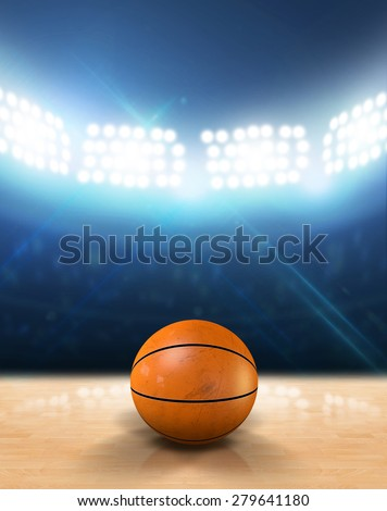 An indoor basketball court with an orange ball on an unmarked wooden floor under illuminated floodlights - stock photo