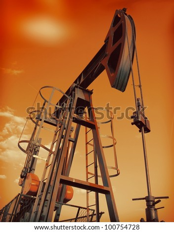 An industrial oil pump under a hot sky - stock photo