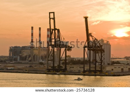 An industrial shipping area on the coast at sunrise or sunset - stock photo