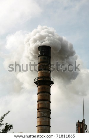 an industrial smoke stack belches out noxis smoke and crud including dreaded CO2 and other global warming gasses freely into the automosphere quickly ruining our earth and enviroment for all - stock photo