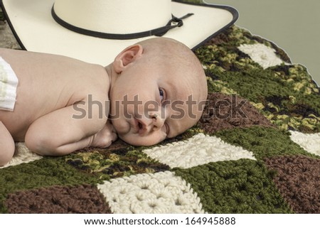 An infant baby laying down surrounded by a cowboy hat. - stock photo