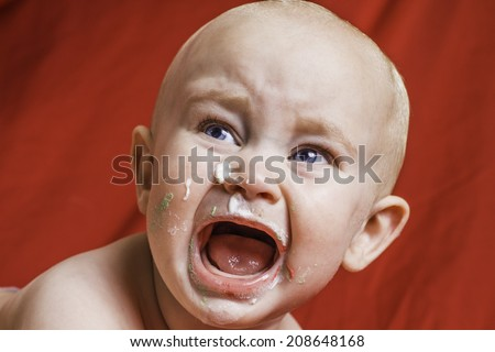 An infant boy crying with birthday cake on his face. - stock photo