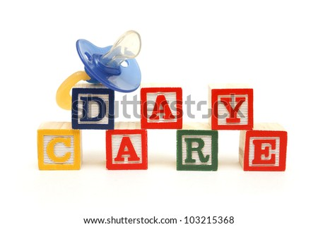 An infants pacifier next to the words day care. - stock photo