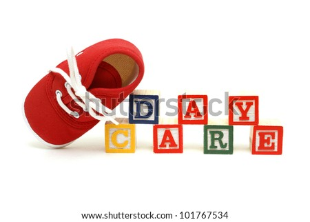 An infants shoe next to the words day care. - stock photo