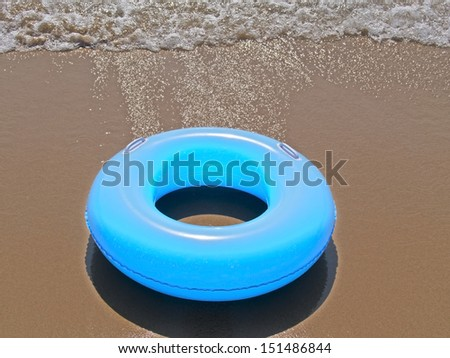 an inflatable donut on the seashore - stock photo