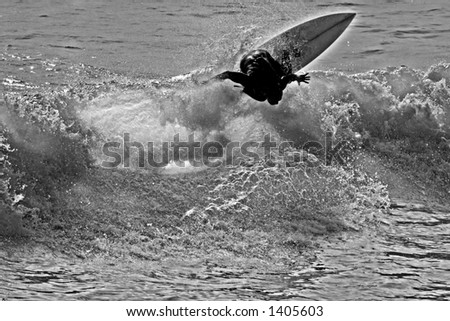 "An ""infrared""  black and white view of a surfer cutting back on a wave."