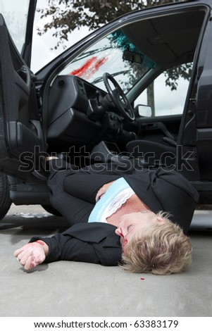 An injured driver with a severe head wound, lies unconsciously on the ground, fallen from her vehicle after an accident - stock photo