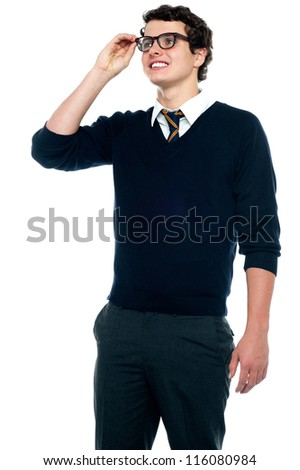 An innocent schoolboy adjusting his eyeglasses to make his vision clear - stock photo