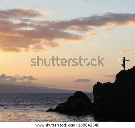 An inspiring silhouette of a man standing on rocks at the ocean