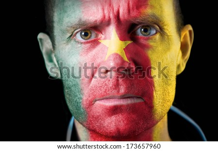 An intense stare from a football fan with their face painted with the Cameroon flag.