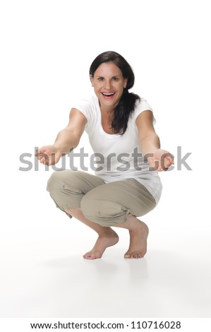 An interactive portrait of an attractive, cheerful brunette mom kneeling down with arms outstretched as if gesturing for a hug toward the camera. Shot in the studio and isolated on a white background. - stock photo