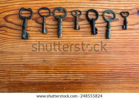 An interesting set of vintage keys on a wooden background - stock photo
