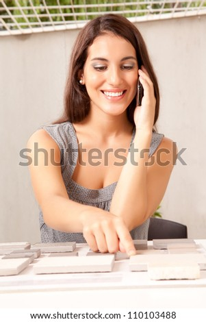 An interior designer / architect on the phone choosing a stone sample swatch - stock photo