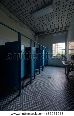 An interior view of a blue hued restroom with sinks and stalls at an abandoned school.