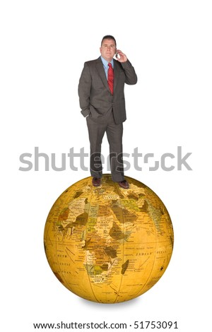 An international businessman standing on a world globe while talking on his cell phone.