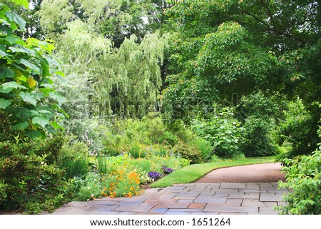An inviting walkway in a manicured park. - stock photo
