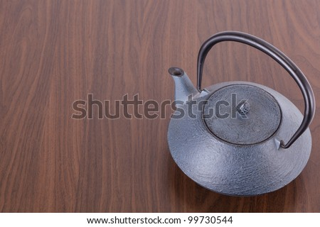An iron teapot is standing on a brown table