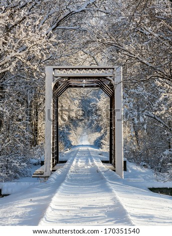 An iron train trestle and railroad tracks are covered with snow in wooded, wintry scene. Photographed in central Indiana. - stock photo