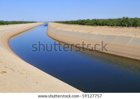 An irrigation canal wends its way through California farmland - stock photo