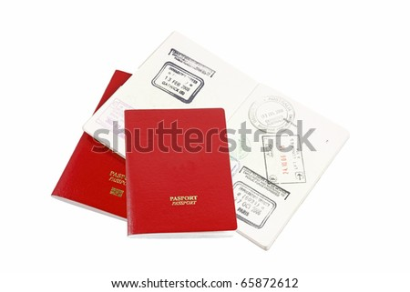 An isolated cutout of three red passport with visa page and immigration stamp. - stock photo