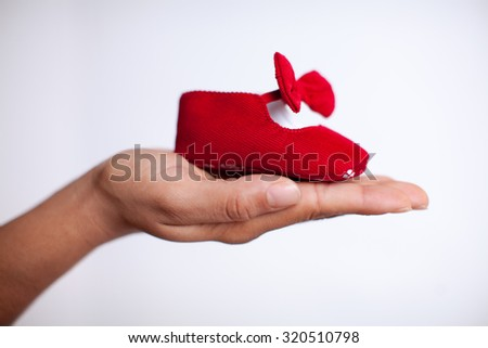 An isolated pair of red baby shoes for the newborn to wear. - stock photo