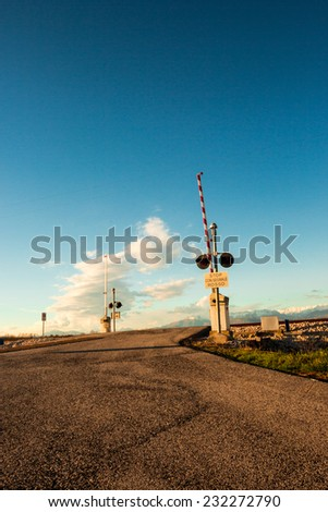 an isolated railroad crossing in the plan of Friuli Venezia-Giulia. Mountains behind. - stock photo