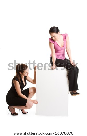 An isolated shot of two businesswomen looking at a blank billboard - stock photo