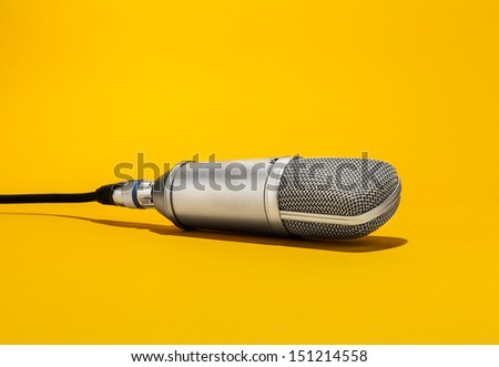 An isolated studio microphone hanging from above by it's cord facing down on a yellow background  - stock photo