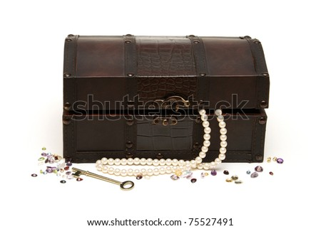 An isolated treasure chest with some loose gemstones and a pearl necklace around it.
