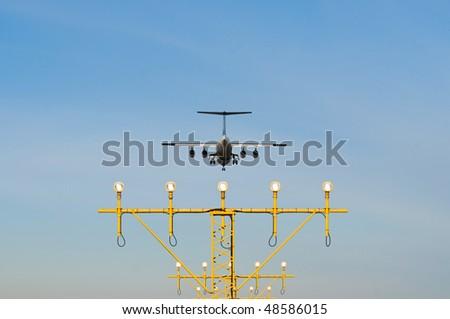 an landing airplane above landing-lights - stock photo